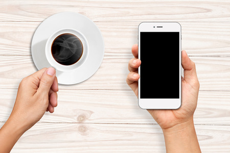 hold on: Hands holding a cup of coffee and White Smart phone on white wooden table