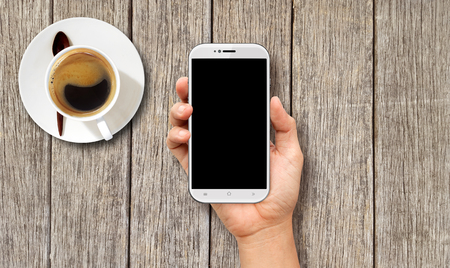 Hand holding White Smart phone on wood coffee table