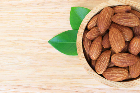 Almonds in wooden bowl on wood table background