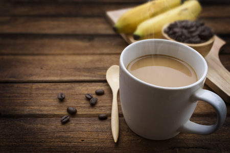 Cup of coffee with coffee beans and banana on wood table
