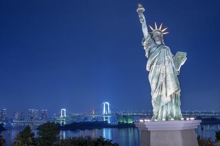 Statue of Liberty and Rainbow bridge at Odaiba Tokyo in twilight
