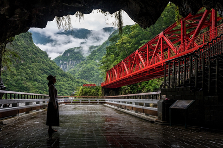 Woman looking at the red bridge in toroko national park in hualien, Taiwan Stock Photo
