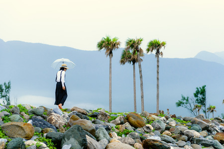 Asian lady with umbrella walking on the rocky beach of hualien, Taiwan