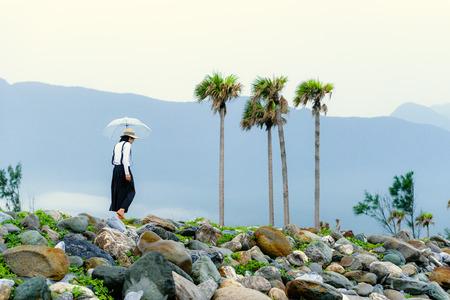 Aziatische dame met paraplu die op het rotsachtige strand van Hualien, Taiwan loopt