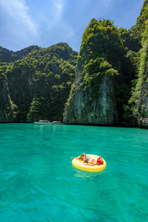 Lady with red hat on yellow pool float chic in beautiful crystal clear water at Pileh bay at Phi Phi island near Phuket, Thailand