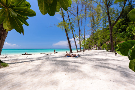 Ladies lie on the sand at beautiful beach of bamboo island near Phi Phi islands in Krabi, Thailand