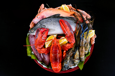 Fresh seafood, lobster, prawn, fish, crab, squid in the wooden bowl with black background. Ready for BBQ.