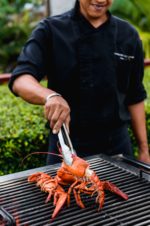 Chef in black shirt doing grilled lobster Stockfoto