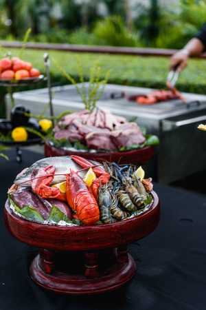 Fresh seafood, lobster, prawn, fish, crab, squid & meat in the wooden bowl ready for grill.