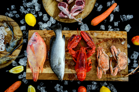 BBQ ingredient; fish, squid, lobster, shrimp, vegetable and ice on black background Stock Photo