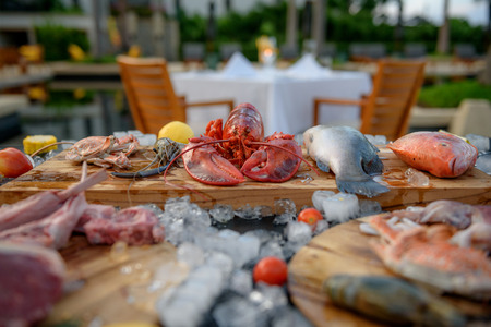 BBQ ingredient; fish, squid, lobster, shrimp, vegetable and ice and background of dining table Stockfoto
