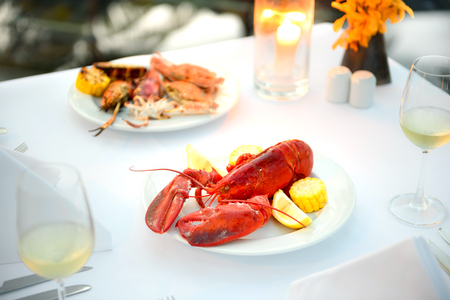 Luxury romantic candle light dinner setup by the pool with plate of lobster and seafood BBQ