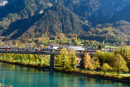Red Swiss train passing bridge over the crytal clear river near Interlaken