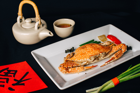 Concept picture for Chinese new year table set up and Chinese deish, crab in curry with Chinese word means fortune