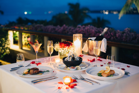 Romantic candlelight dinner table setup for Valentines day with Champaign & wine glasses and special dishes Stockfoto