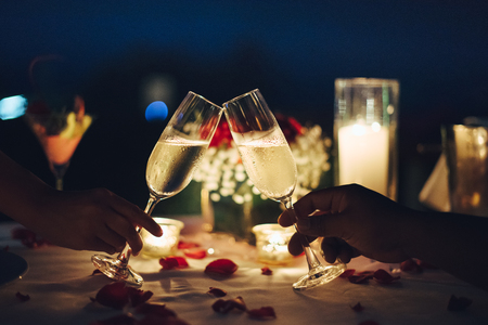 Romantic candlelight dinner table setup. Man & Woman hold glass of Champaign. Stockfoto
