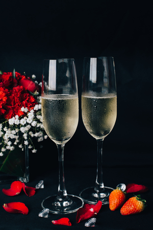 Concept picture for Valentines day. 2 glasses of Champaign with rose petal, strawbery and flower