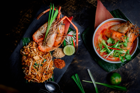 Concept pictures of famouse Thai dishes, Tom Yum Kung & Phad Thai. Beautiful presentation on black stone and black background. Stockfoto