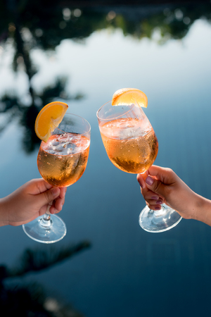 Concept picture of a couple holding glasses of cocktail and cheers by the swiming pool to celebrate their success. Stockfoto