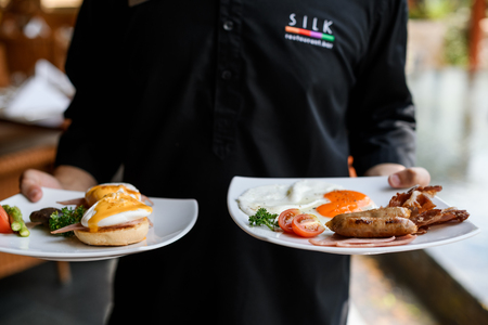 Concept picture, staff is holding a egg benedict for breakfast