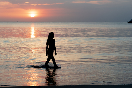Attractive sexy women walking on the beach during sunset time