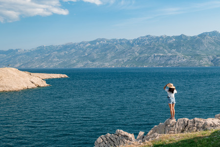 Concept picture of traveling. Woman looking at scenic view by the sea at pag island in Croatia, Stok Fotoğraf