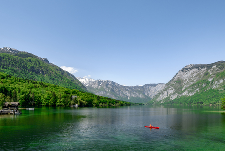 Concept picture of summer time at lake bohinj in Slovenia with red canoe in emerald color lake.