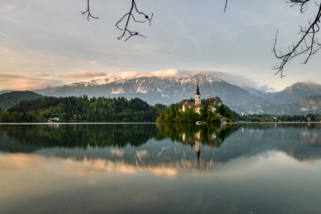 Amazing sunset time at famous Bled lake with church on the small island and a background of bled castle Editorial