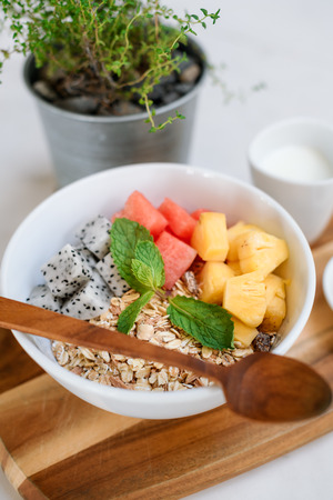 Bowl of Asian heathy breakfast from top view includes grain dragon fruit, pine apple, papaya and cup of milk and honey