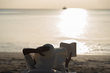 Woman with white hat sit on the beach reading the booking during sunset. Stockfoto