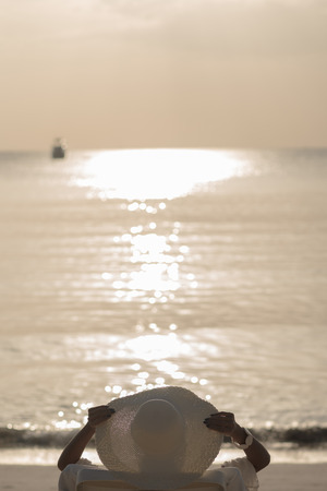 Woman with white hat sit on the beach looking at sunset. Stockfoto