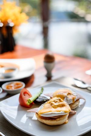 Egg benedict for breakfast on the table in hotel restaurant