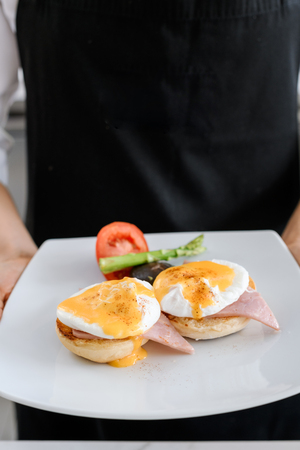 Concept picture, chef is holding a egg benedict for breakfast