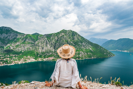 Concept picture of traveling, woman with hat looking at view of famous Gospa-od-Shkrpjela from a birds-eye view of the Boko-Kotor Bay in Montenegro Stok Fotoğraf