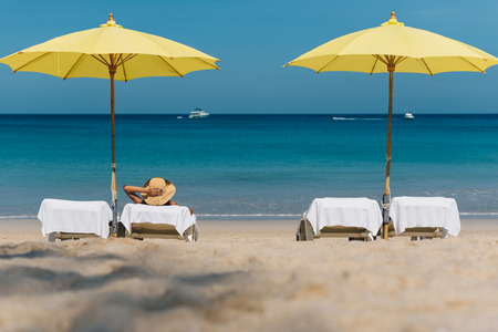 A women sitting on beach chair under colorful yellow beach umbrella with a background of beautiful Andaman sea in Phuket, Thailand