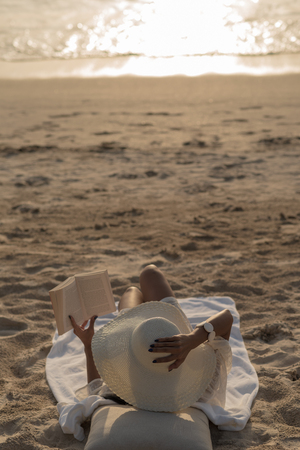 Woman with white hat sit on the beach reading the booking during sunset. Stok Fotoğraf