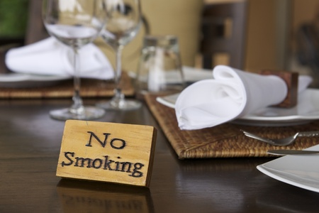 manner: wooden no smoking sign on restaurant table