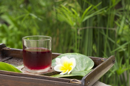 welcome drink in resort and spa, herbal drink with green leaf, white and yellow flower on traditional wood tray photo