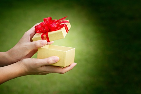 Gift box opening hand with glowing aura and text space
