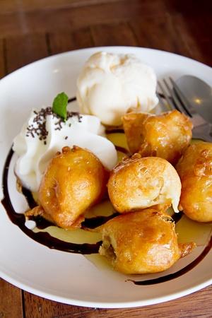 banana fritter with vanilla ice cream and whip cream and chocolate sauce
