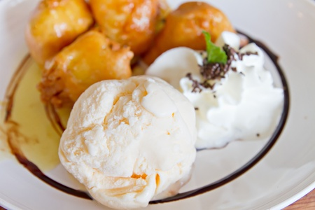 vanilla ice cream with deep fried banana fritter and whip cream and chocolate sauce Stock Photo