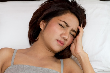sick woman sleep with pain or headache on bed