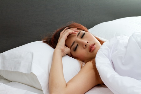 sick woman on bed, symptom of cold, flu, insomnia, stress, headache, hangover, dizziness Stock Photo