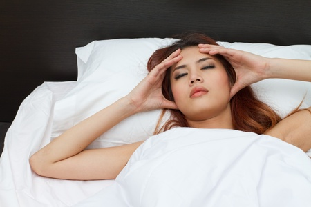 sick woman on bed massaging her head to relieve pain or stress photo