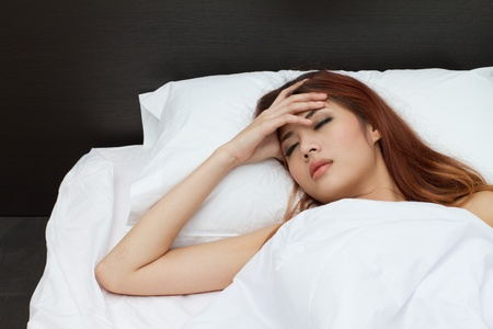woman sleep and hold her head with subliminal stress or other possible symptoms photo