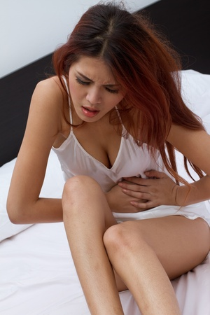 woman with menstruation pain or stomach trouble in bedroom Stock Photo
