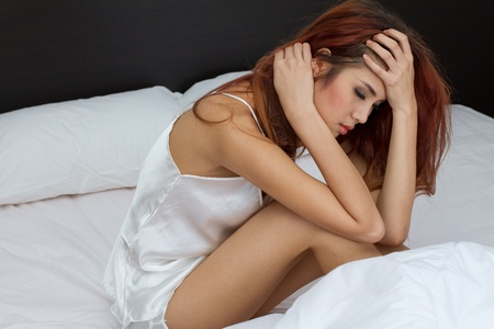 woman sitting on bed with accumulated stress, worry, loneliness, mental problem or sickness Stock Photo