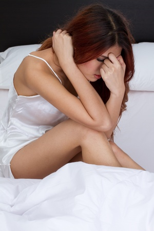 woman on bed with stress, worry, loneliness, mental problem or sickness with text space below