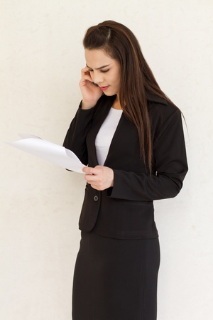 female business executive looking at the document and talking via cellphone with stress photo