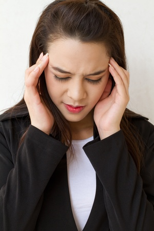 exhausted: woman with headache, migraine, stress, insomnia, hangover in business executive dress Stock Photo